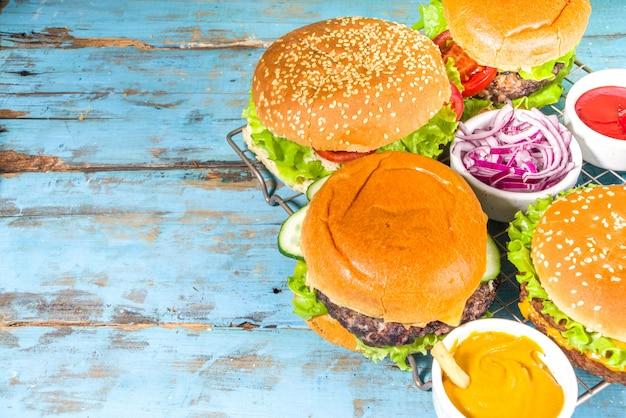 Hamburger americani tradizionali assortiti, con salse e patatine fritte su fondo di legno blu