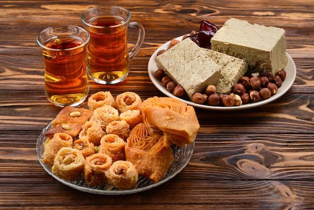 Dolci orientali tradizionali assortiti con tè su superficie di legno