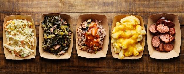 Vassoi assortiti di texas bbq con cavolo, hotlink, maiale stirato, mac e formaggio, insalata di cavolo
