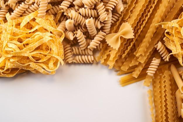 Varietà assortite di carta da parati per pasta. mescolare maccheroni, spaghetti su sfondo bianco con spazio di copia
