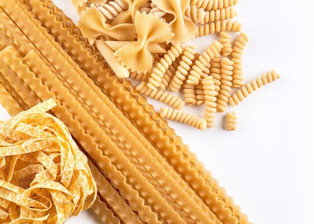 Varietà assortite di carta da parati per pasta. mescolare maccheroni, spaghetti su fondo bianco