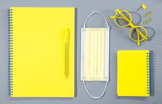 Forniture per ufficio di cancelleria per ufficio e scuola gialla assortite con occhiali e maschera medica su sfondo grigio.