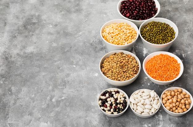 Assortimento di fagioli (lenticchie rosse, lenticchie verdi, ceci, piselli, fagioli rossi, fagioli bianchi, fagioli misti, fagioli verdi) su spazio grigio. copia spazio. spazio alimentare