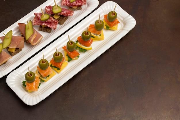 Assortimento di tartine con salmone, pancetta, formaggio, sottaceti sulla piastra bianca, vista dall'alto,