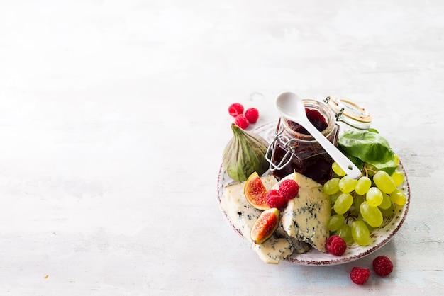 Assortimento di formaggio, frutti di bosco e uva con vino rosso in bicchieri sulla superficie della pietra