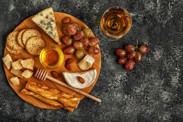 Assortimento di formaggio con vino, miele, noci e uva su un tagliere.