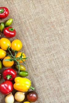 Assortimento di verdure fresche colorate su sfondo di tela di sacco. vista piana laico e dall'alto. copia spazio.