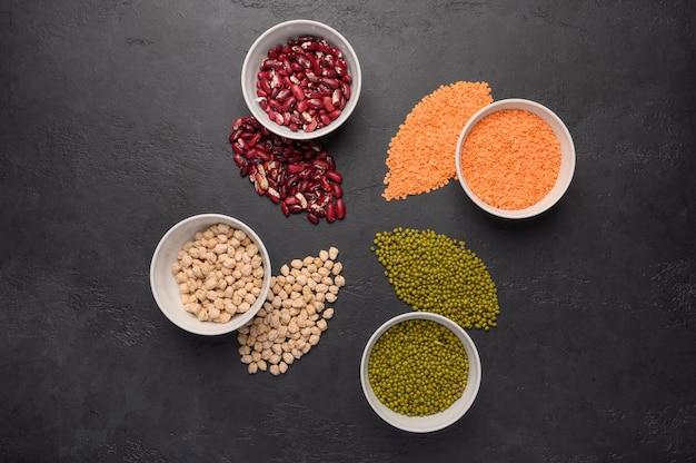 Assortimento di legumi colorati in ciotole lenticchie fagioli ceci purè sulla superficie in calcestruzzo vista dall'alto