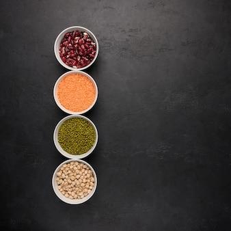 Assortimento di legumi colorati in ciotole lenticchie fagioli ceci purè sulla superficie scura vista dall'alto