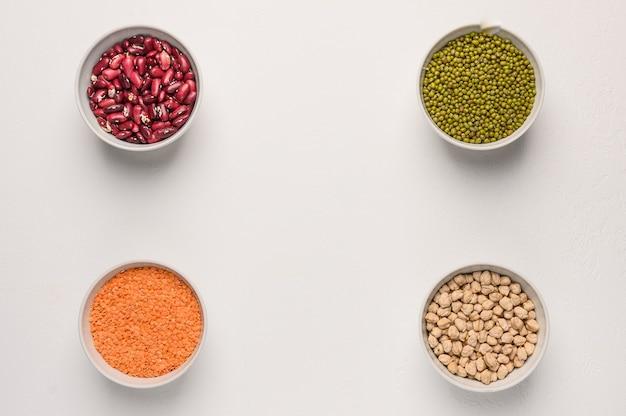 Assortimento di legumi colorati in ciotole lenticchie fagioli ceci purè sulla superficie bianca vista dall'alto