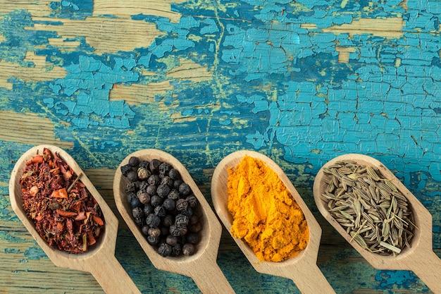 Assortimento di spezie colorate in cucchiai di legno.