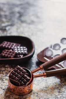 Assortimento di diversi tipi di cioccolato, piatto in legno intagliato, con oggetti di scena vintage sulla superficie