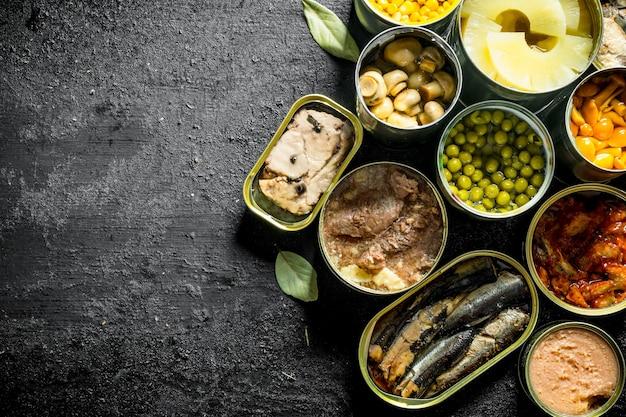 Assortimento di diversi tipi di cibo in scatola in lattine sul tavolo rustico nero