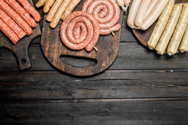 Assortimento di diverse salsicce crude. su uno sfondo di legno.