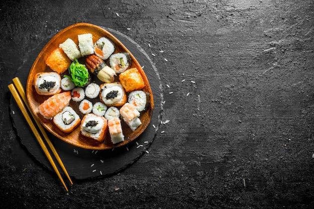Assortimento di diversi rotoli di sushi su un piatto con le bacchette sul tavolo rustico nero