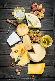 Assortimento di diversi tipi di formaggio con uva e vino bianco sul tavolo rustico.