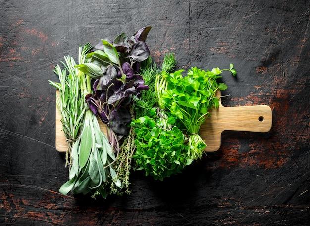 Assortimento di diversi tipi di erbe per insalata sul tavolo rustico