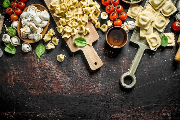 Un assortimento di diversi tipi di pasta grezza. su rustico scuro