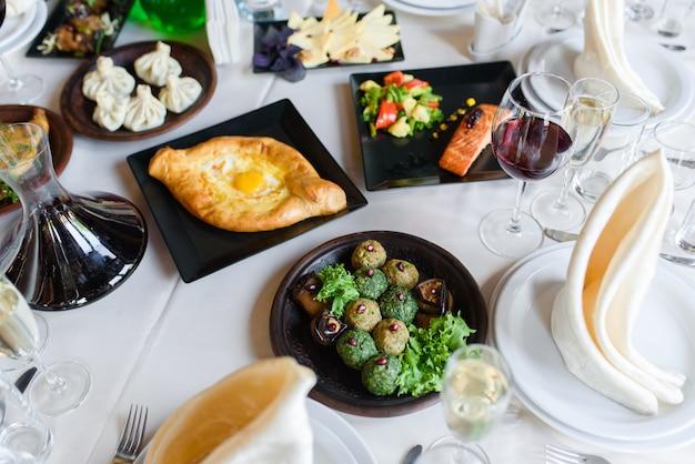 Assortimento di piatti phali, khachapuri, salmone, khinkali, ciotola per apparecchiare la tavola con vino, bicchieri, piatti, tovaglioli