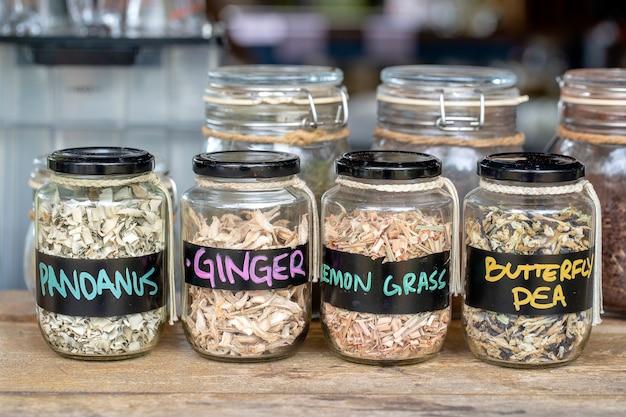 Assortimento di spezie essiccate in bottiglie di vetro su fondo di legno. zenzero secco, pandanus, citronella e pisello farfalla in barattoli di vetro, primo piano