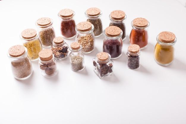 Assortimento di spezie secche in bottiglie di vetro vintage su sfondo bianco