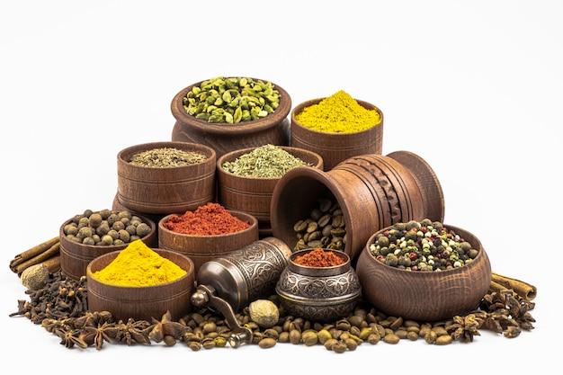 Assortimento di spezie e condimenti orientali in stoviglie di legno da vicino isolato su uno sfondo bianco.