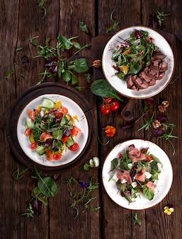 Assortimento di insalate di verdure fresche distese. vista dall'alto sul buffet vegetariano con gustosa varietà di contorni. set di cibo sano