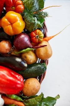 Assortimento di verdure fresche in un cesto, cibo biologico sano e biologico su sfondo bianco, stile mercato di campagna, prodotti dell'orto, cibo vegetariano dietetico, alimentazione pulita. Foto Premium