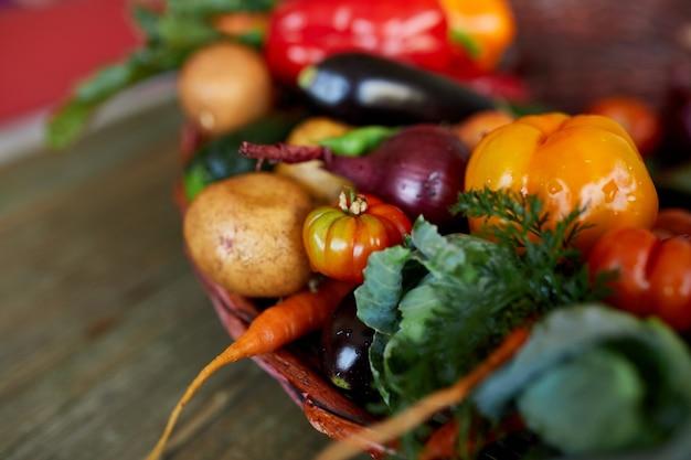 Assortimento di verdure fresche in un cesto, cibo bio sano e biologico su fondo in legno, stile mercato di campagna, prodotti dell'orto, cibo vegetariano dietetico, alimentazione pulita.