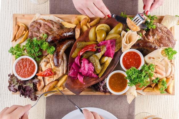 Assortimento di carne fritta, patate, salsicce, sottaceti, pomodori, peperoni, erbe aromatiche, lavash su un vassoio di legno sul tavolo. vista dall'alto.