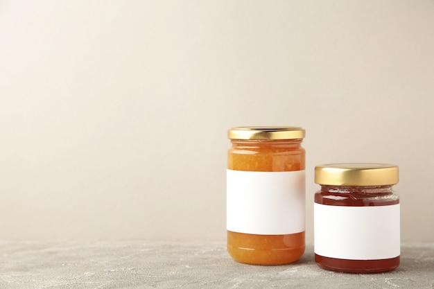 Assortimento di vasetti di marmellata mock-up. vasetti con etichetta vuota su grigio. vista dall'alto