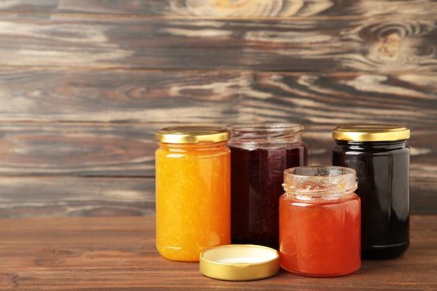 Assortimento di marmellate su sfondo marrone con copia spazio.