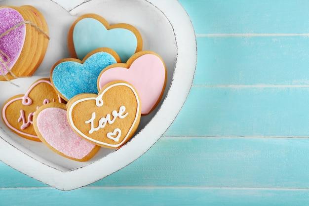 Assortimento di biscotti d'amore in scatola su sfondo blu, primo piano