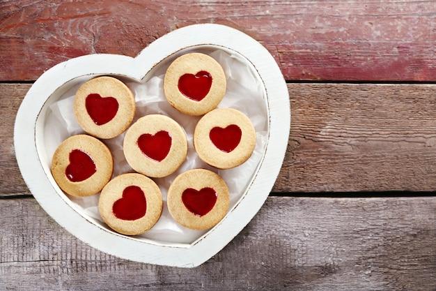 Assortimento di biscotti d'amore in scatola su fondo di legno, primo piano