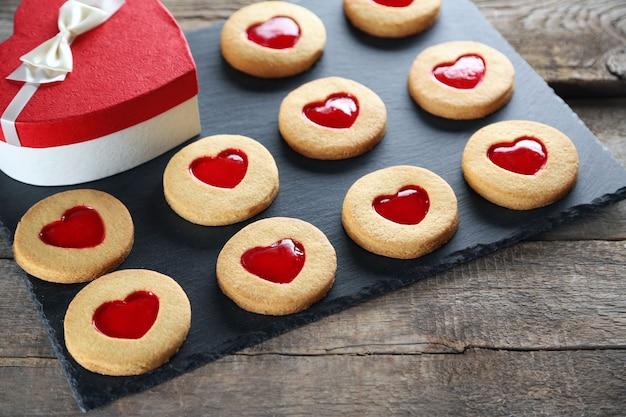 Assortimento di biscotti d'amore con confezione regalo su supporto grigio