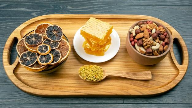 Assortimento di noci e agrumi secchi assortiti e miele floreale fresco a nido d'ape su tavola di legno da cucina. alimento vitaminico utile per il corpo umano