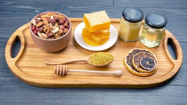Assortimento di noci e agrumi secchi assortiti e miele e polline floreali freschi a nido d'ape su tavola di legno da cucina. alimento vitaminico utile per il corpo umano