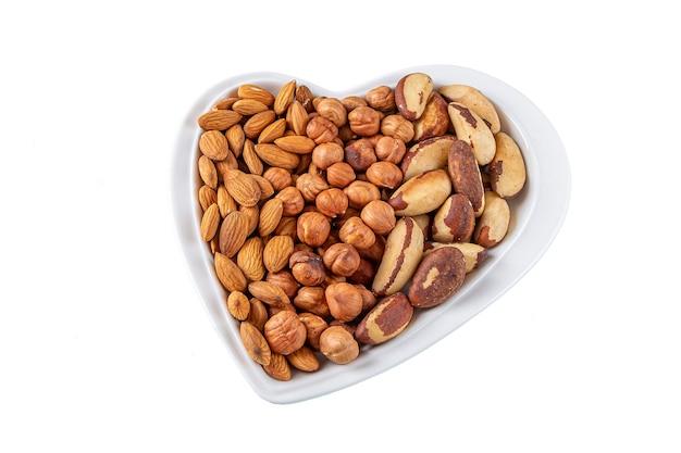 Assortimento di noci nocciole, mandorle, noci pecan nel piatto a forma di cuore isolato su bianco