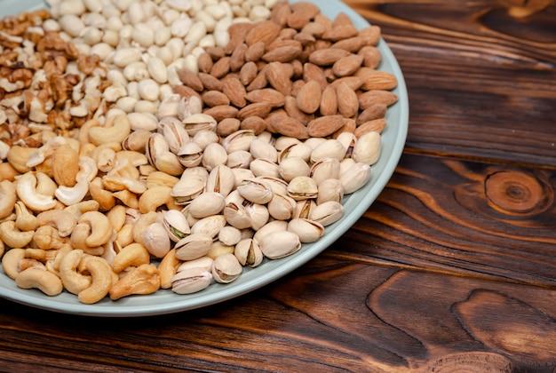 Assortimento di noci su un piatto. tavola di legno. snack salutare. disteso