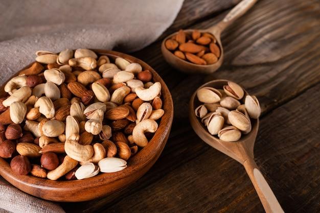 Assortimento di noci in ciotola di legno sul tavolo di legno scuro. anacardi, nocciole, mandorle e pistacchi.