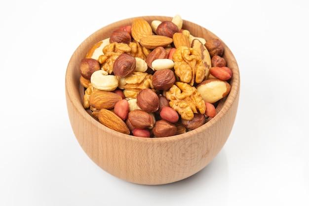 Assortimento di noci in un piatto di legno su sfondo bianco. cibo biologico vitaminico