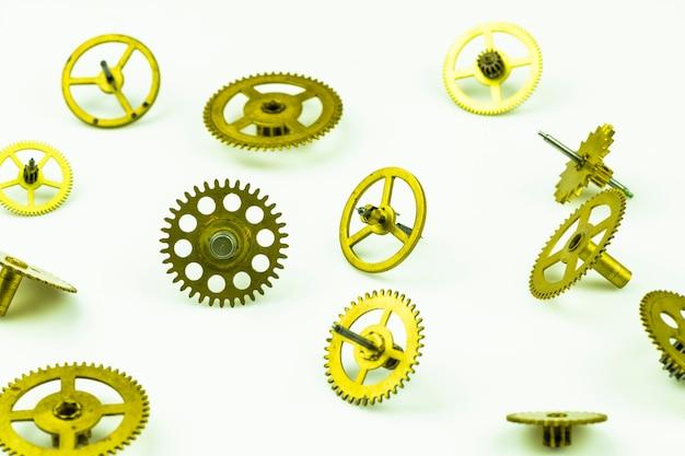 Un assortimento di vecchi ingranaggi di un orologio in bronzo isolato su uno sfondo bianco.