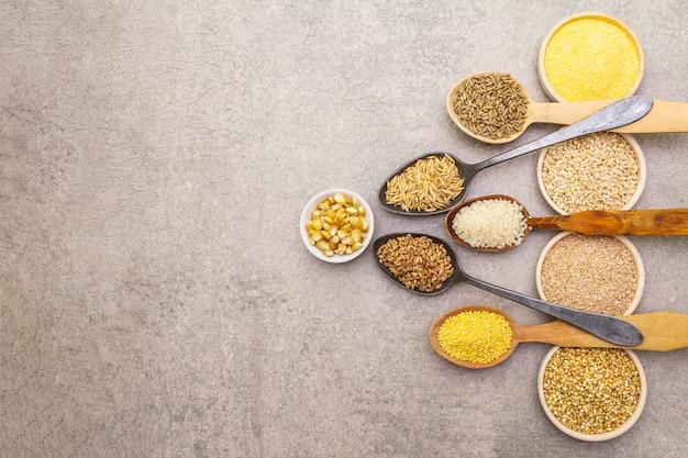 Assortimento di cereali biologici, legumi e cereali integrali in ciotole e cucchiai
