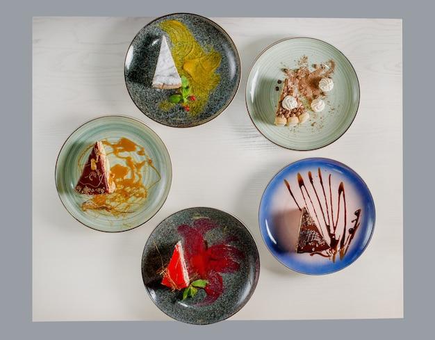 Assortimento di pezzi di torta sul tavolo, copia dello spazio. diverse fette di deliziosi dessert, concetto di menu del ristorante, vista dall'alto.