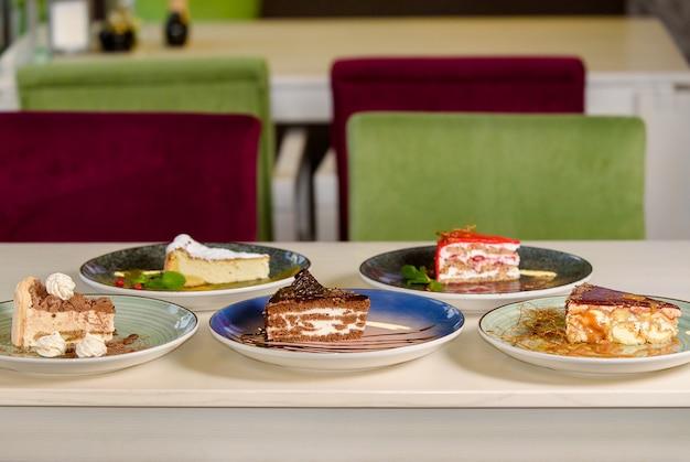 Assortimento di pezzi di torta sul tavolo, copia dello spazio. diverse fette di deliziosi dessert, concetto di menu del ristorante.
