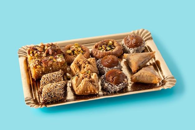 Assortimento di baklava dessert ramadan sulla superficie blu. dolci arabi tradizionali.