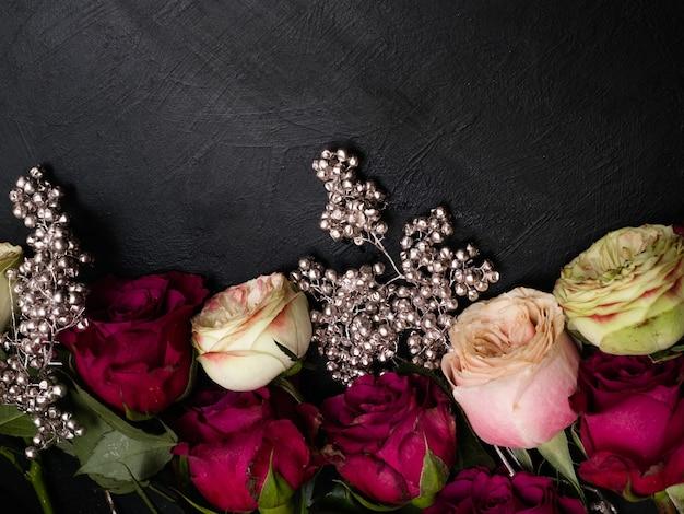 Assortimento di rose rosse e rosa con decorazioni di perline d'argento su sfondo scuro. bellissimo disegno floreale. amore e bellezza. copia il concetto di spazio