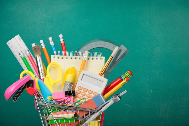 Assortimento di materiale scolastico nel carrello della spesa sullo sfondo