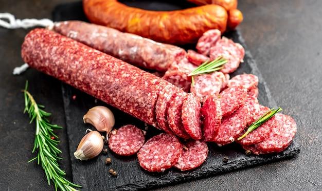 Assortimento di salsicce affumicate e salsicce con stampo su un tavolo di pietra