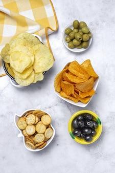 Assortimento di snack a casa con patatine fritte, birra, cracker, olive verdi e nere sul tavolo di marmo